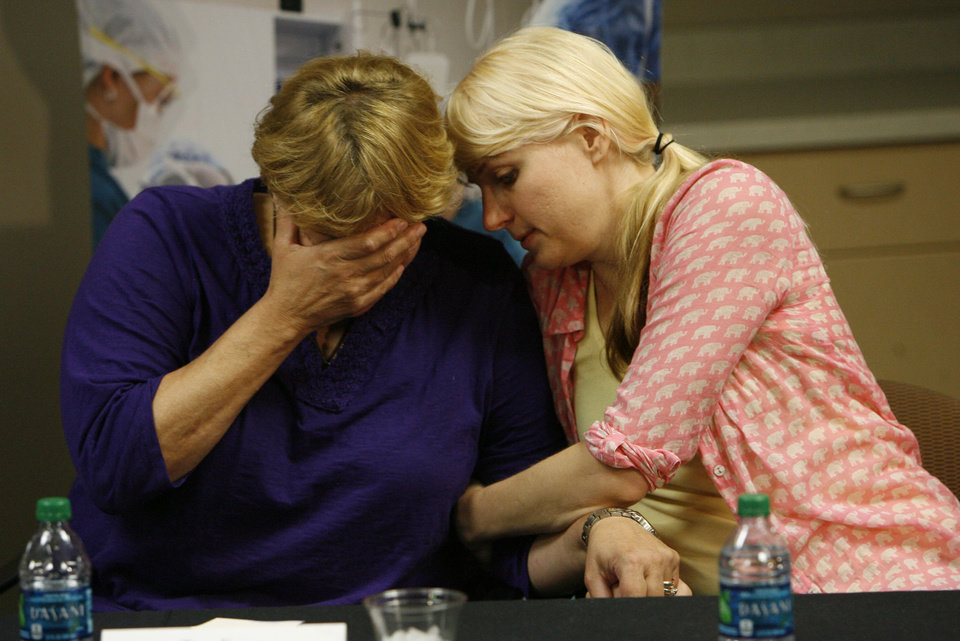 Photo - Tara Evans, left, is comforted by her daughter Karen Evans during a news conference at the McKay-Dee Hospital Center in Ogden, Utah on Monday, June 17, 2013, to update the condition of Tara's husband, James Evans, who was shot in the head during church services on Sunday. James Evans, 65, was in critical condition Monday, but has made steady progress, said intensive care unit director Dr. Barbara Kerwin. (AP Photo/The Salt Lake Tribune, Francisco Kjolseth)  DESERET NEWS OUT; LOCAL TV OUT; MAGS OUT