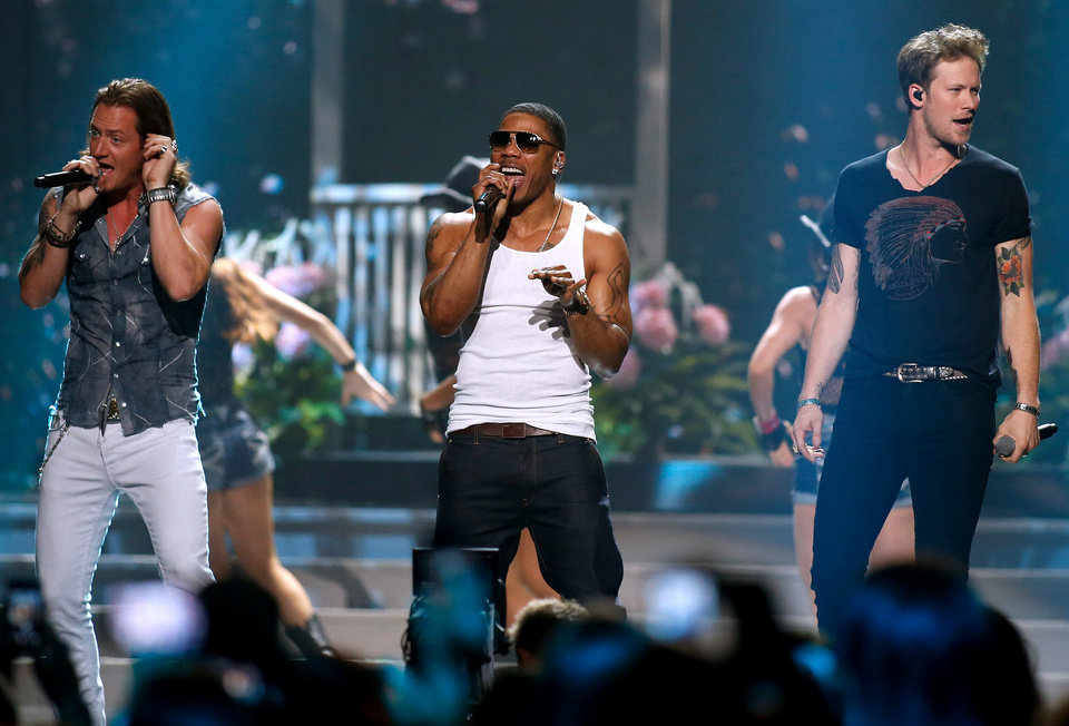 Photo - Tyler Hubbard, left, and Brian Kelley, right, of Florida Georgia Line perform with Nelly, center, during the Miss USA 2014 pageant in Baton Rouge, La., Sunday, June 8, 2014. (AP Photo/Jonathan Bachman)