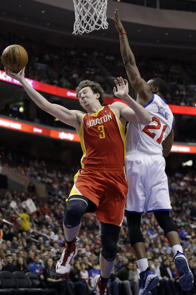 Houston Rockets' Omer Asik, left, of Turkey, goes up for a shot against Philadelphia 76ers' Thaddeus Young in the first half of an NBA basketball game, Saturday, Jan. 12, 2013, in Philadelphia. (AP Photo/Matt Slocum)