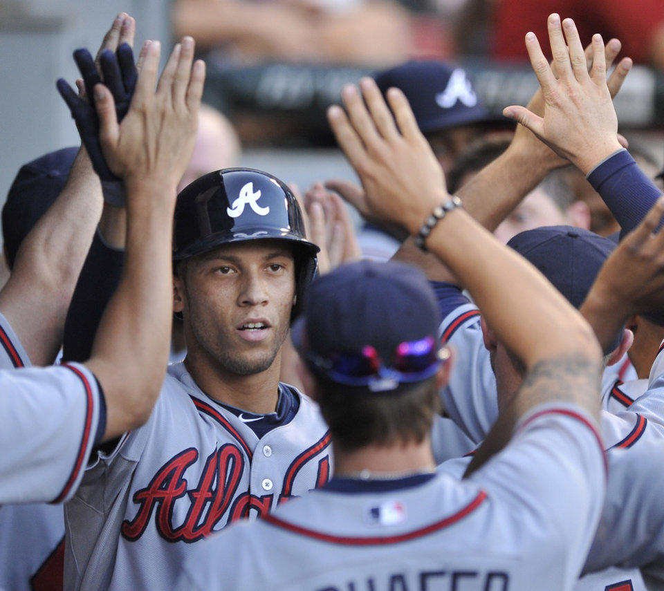 Photo - Atlanta Braves' Andrelton Simmons celebrates with teammates in the dugout after hitting a two-run home run during the third inning of a baseball game against the Chicago White Sox in Chicago, Friday, July 19, 2013. (AP Photo/Paul Beaty)