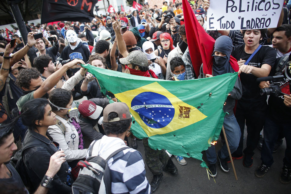 Photo - Demonstrators burn a Brazilian flag during a protest against the 2014 World Cup in Belo Horizonte, Brazil, Thursday, June, 12, 2014. The sign in the upper right reads in Portuguese
