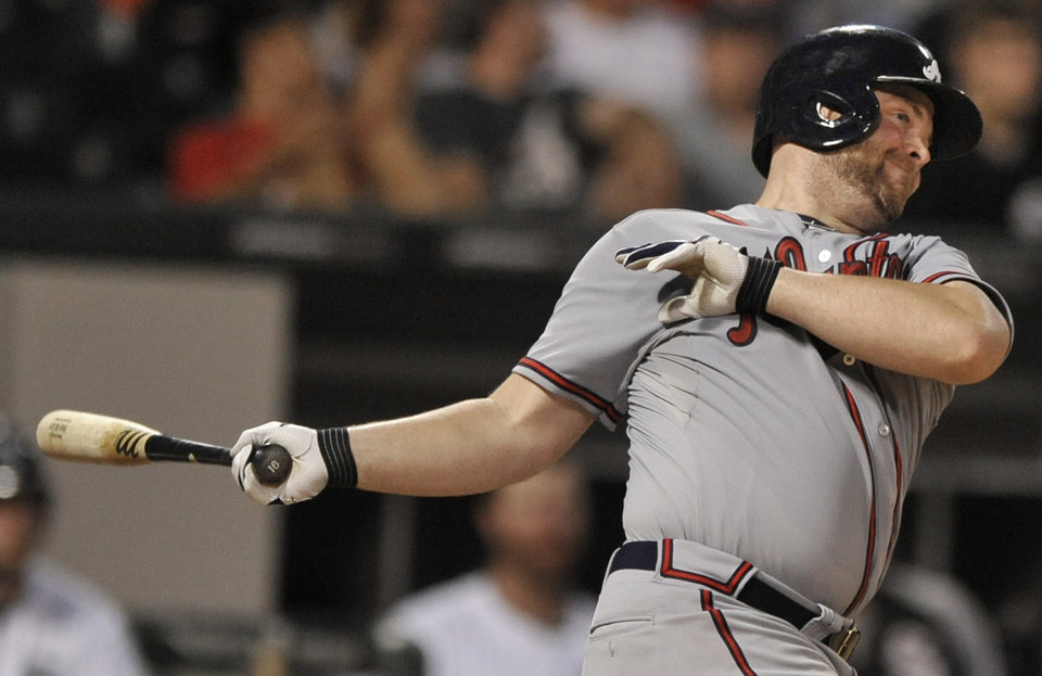 Photo - Atlanta Braves' Brian McCann watches his three-run home run during the sixth inning of a baseball game against the Chicago White Sox in Chicago, Friday, July 19, 2013. (AP Photo/Paul Beaty)