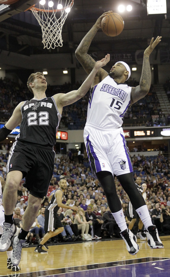Photo - Sacramento Kings center DeMarcus Cousins, right, grabs a rebound away from San Antonio Spurs center Tiago Splitter, of Brazil, during the first quarter of an NBA basketball game in Sacramento, Calif., Friday, March 21, 2014.(AP Photo/Rich Pedroncelli)