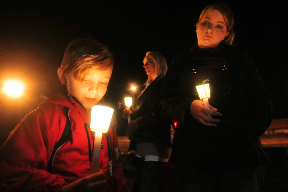 Photo - Cade Smith, 6, watches the flame of his candle burn as his mother, Brandi, looks on during a candlelight vigil for the families involved in the ongoing hostage crisis Friday night, Feb. 1, 2013 in Midland City, Ala. The Smith family feels a connection to the autistic boy named Ethan being held hostage because their son, Cade, also has autism. (AP Photo/The Dothan Eagle, Jay Hare)