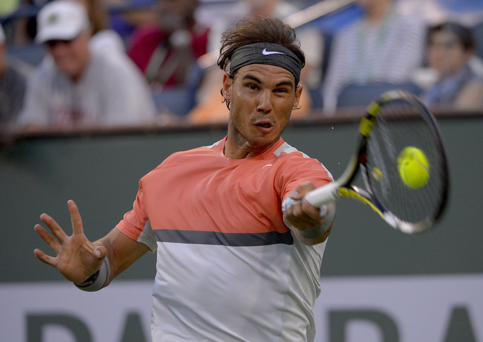 Photo - Rafael Nadal, of Spain, hits to Alexandr Dolgopolov, of Ukraine, during a third round match at the BNP Paribas Open tennis tournament, Monday, March 10, 2014 in Indian Wells, Calif. (AP Photo/Mark J. Terrill)