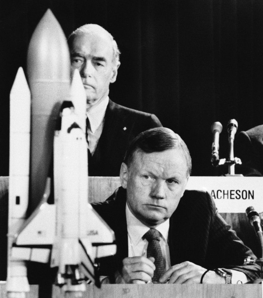 Photo - In this Feb. 11, 1986, file photo, former astronaut Neil Armstrong, a member of the presidential panel investigating the Space Shuttle Challenger explosion, listens to testimony before the commission in Washington. David Acheson, a commission member, listens in the background. A model of the shuttle sits on the table. (AP Photo/Scott Stewart)