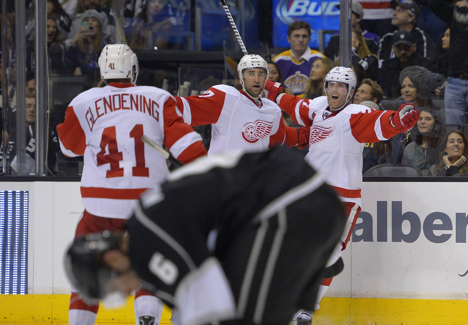 Photo - Detroit Red Wings left wing Tomas Tatar, upper right, of Slovenia, celebrates his goal with teammates right wing Luke Glendening, upper left, and defenseman Kyle Quincey as Los Angeles Kings defenseman Jake Muzzin skates by during the third period of an NHL hockey game, Saturday, Jan. 11, 2014, in Los Angeles. (AP Photo/Mark J. Terrill)