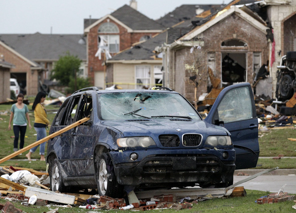 Photo -   A damaged vehicle is seen as area residents survey the tornado damage to their neighborhood Tuesday, April 3, 2012, in Forney, Texas. Tornadoes tore through the Dallas area Tuesday, peeling roofs off homes, tossing big-rig trucks into the air and leaving flattened tractor trailers strewn along highways and parking lots. (AP Photo/Tony Gutierrez)