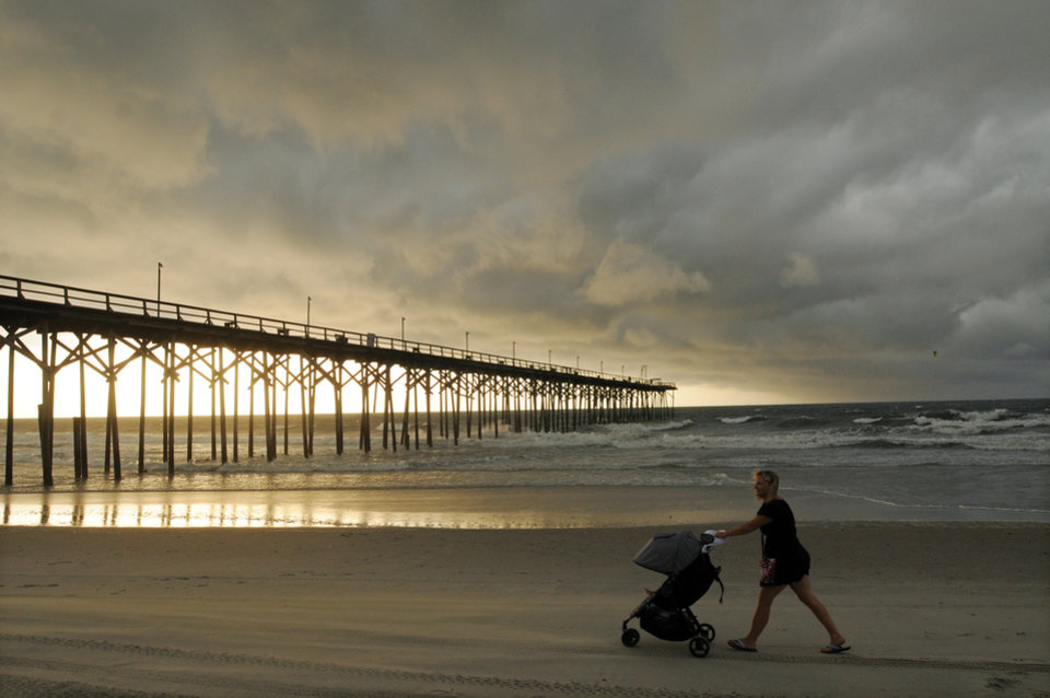 Photo - Clouds and rains move in as beachgoers walk along the shore of the north end of Carolina Beach, N.C., Thursday, July 3, 2014. Residents along the coast of North Carolina are bracing for the arrival of the Hurricane Arthur, which threatens to give the state a glancing blow on Independence Day. (AP Photo/Wilmington Star-News, Mike Spencer)
