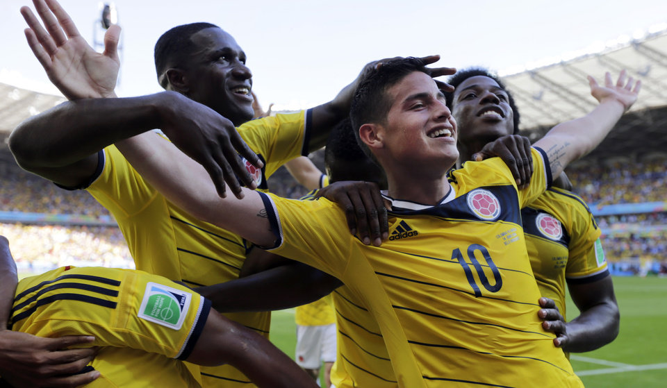 Photo - In this Saturday, June 14, 2014 photo, Colombia's James Rodriguez, front, center right, celebrates with his teammates after scoring his side's third goal during the group C World Cup soccer match against Greece at the Mineirao Stadium in Belo Horizonte, Brazil. Colombia defeated Greece 3-0. (AP Photo/Fernando Vergara)