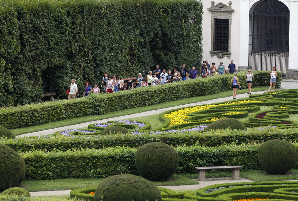 Photo - In this Aug. 7, 2014, photo, tourists stroll through UNESCO's Flower Garden in city of Kromeriz, Czech Republic. With its original geometrical layout and high topiary walls, it's a rare example of an early Baroque garden style. And it's now reclaiming the unique features it had when it was completed in 1675, including labyrinths, fountains, sculptures inspired by Greek and Roman mythology, a Dutch bulb garden and citrus trees. (AP Photo/Petr David Josek)