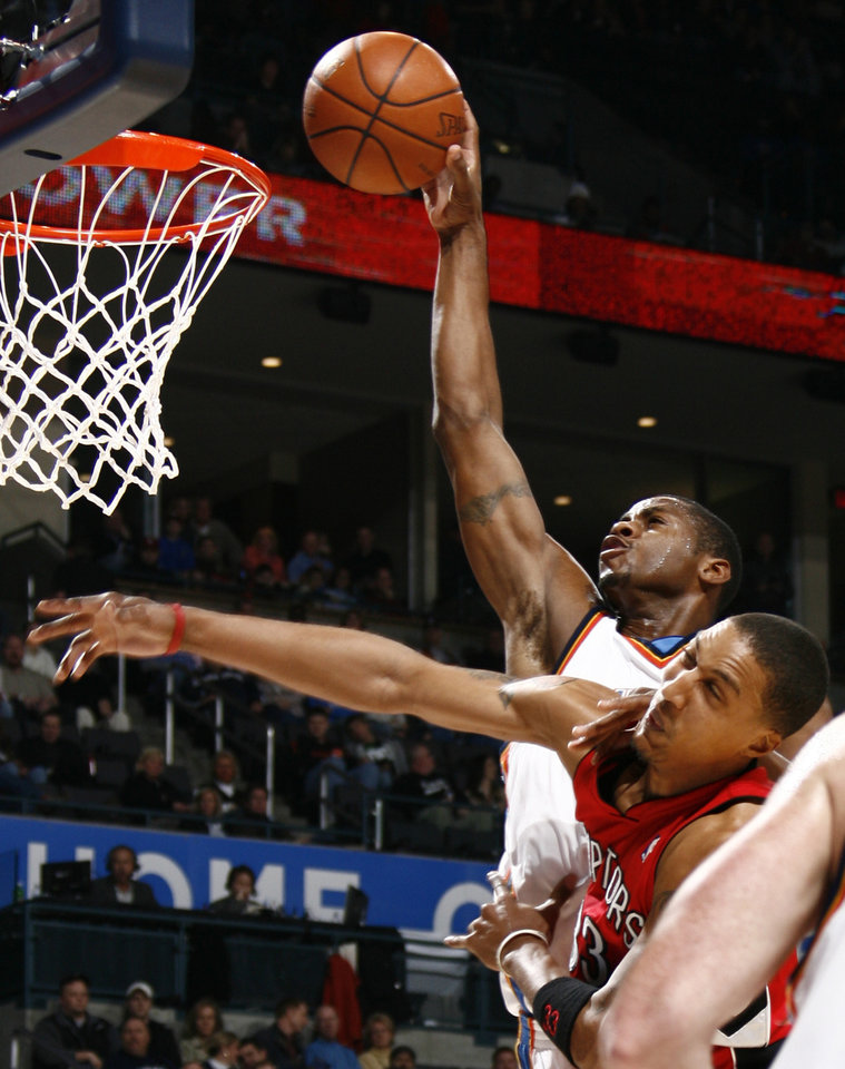 Photo - Oklahoma City's Desmond Mason dunks the ball over Jamario Moon of Toronto in the first half during the NBA basketball game between the Toronto Raptors and the Oklahoma City Thunder at the Ford Center in Oklahoma City, Friday, Dec. 19, 2008. BY NATE BILLINGS, THE OKLAHOMAN ORG XMIT: KOD