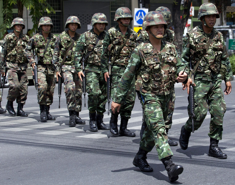Photo - Thai soldiers patrol near the Army Club before former Prime Minister Yingluck Shinawatra arrives to report to Thailand's ruling military in Bangkok, Thailand, Friday, May 23, 2014. The military on Friday summoned the entire ousted government and members of the politically influential family at the heart of the country's long-running conflict, a day after it seized control of this volatile Southeast Asian nation in a non-violent coup. It was unclear why more than 100 people,  including the ousted prime minister and several members of the influential Shinawatra family, were ordered to report to the military, which said it was summoning the high-profile figures