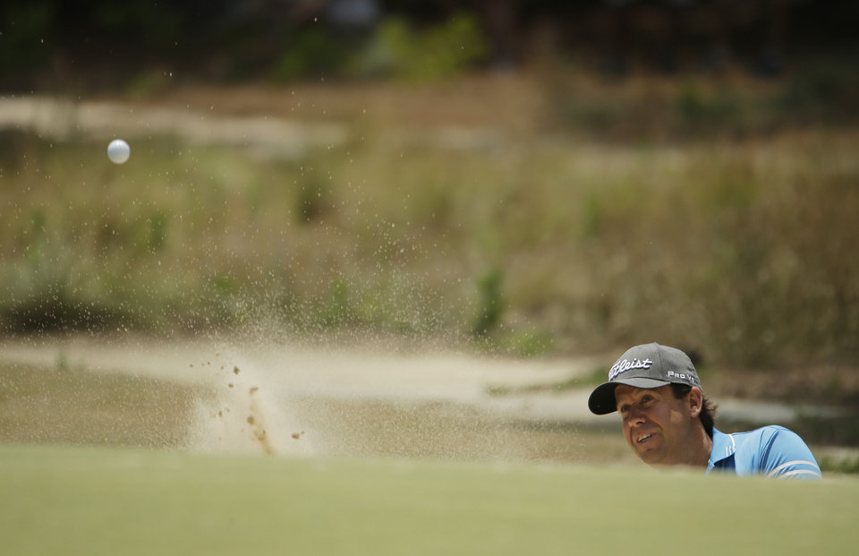 Photo - Erik Compton hits out of the bunker on the first hole during the third round of the U.S. Open golf tournament in Pinehurst, N.C., Saturday, June 14, 2014. (AP Photo/Chuck Burton)
