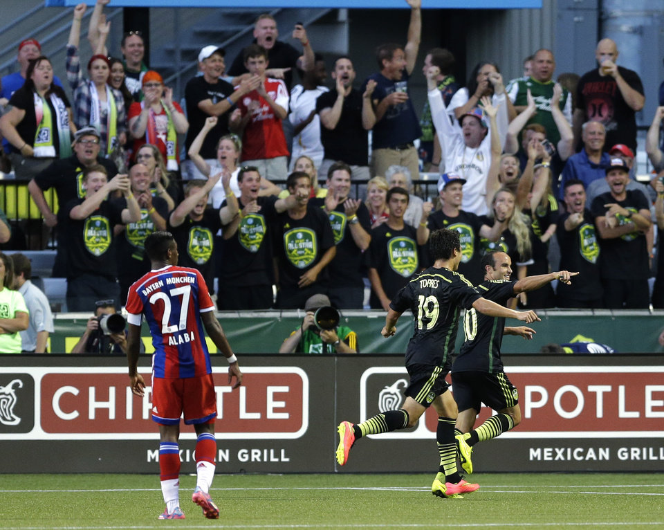 Photo - Los Angeles Galaxy forward Landon Donovan, right, celebrates with Chivas USA forward Erick Torres (19) as Bayern Munich's David Alaba (27) watches, after Donovan scored the go-ahead goal in the second half of the MLS All-Star soccer game, Wednesday, Aug. 6, 2014, in Portland, Ore. The MLS All-Stars won 2-1. (AP Photo/Ted S. Warren)
