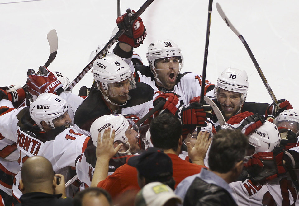 Photo -   The New Jersey Devils celebrate after defeating the Florida Panthers on a goal by Adam Henrique, lower right, during the second overtime of Game 7 in a first-round NHL Stanley Cup playoff hockey series, in Sunrise, Fla., Wednesday, April 26, 2012. The Devils won 3-2. (AP Photo/J Pat Carter)