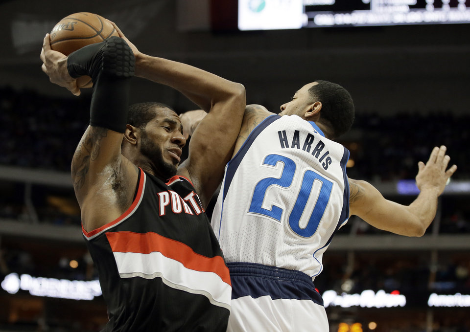 Photo - Portland Trail Blazers forward LaMarcus Aldridge, left, grabs an offensive rebound in front of Dallas Mavericks' Devin Harris (20) during the first half of an NBA basketball game, Saturday, Jan. 18, 2014, in Dallas. (AP Photo/Tony Gutierrez)