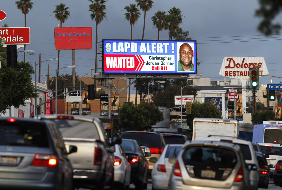 "A digital billboard along Santa Monica Boulevard on the west side of Los Angeles shows a ""wanted"" alert for former Los Angeles police officer Christopher Dorner Friday, Feb. 8, 2013.  Dorner is suspected in a spree of violence as part of a vendetta against law enforcement after being fired by the department. He is also a suspect in the shooting deaths of a former LAPD captain's daughter and her fiance, and two other shootings that left an officer dead and two others wounded. (AP Photo/Reed Saxon)"