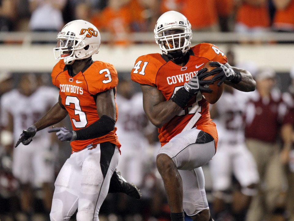 Photo - OSU's Victor Johnson (3) and Orie Lemon (41) celebrate recovering Troy's last fumble of the game during the college football game between the Oklahoma State University Cowboys (OSU) and the Troy University Trojans at Boone Pickens Stadium in Stillwater, Okla., Saturday, Sept. 11, 2010. Photo by Sarah Phipps, The Oklahoman