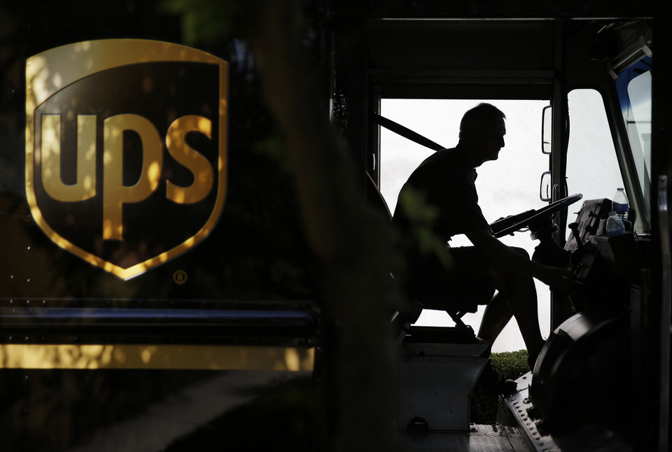 Photo - In this June 20, 2014 photo, United Parcel Service driver Marty Thompson starts his truck up after making a delivery in Cumming, Ga.  UPS reports quarterly earnings on Tuesday, July 29, 2014. (AP Photo/David Goldman)