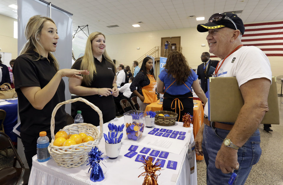 In this photo taken Wednesday, July 16, 2014, job seeker U.S. Army veteran John Godman, right, talks to recruiters Nicole Rushton, left, and Megan Hogan, center, at a Hiring Fair For Veterans in Fort Lauderdale, Fla. The Labor Department releases weekly jobless claims on Thursday, July 23, 2014. (AP Photo/Alan Diaz)