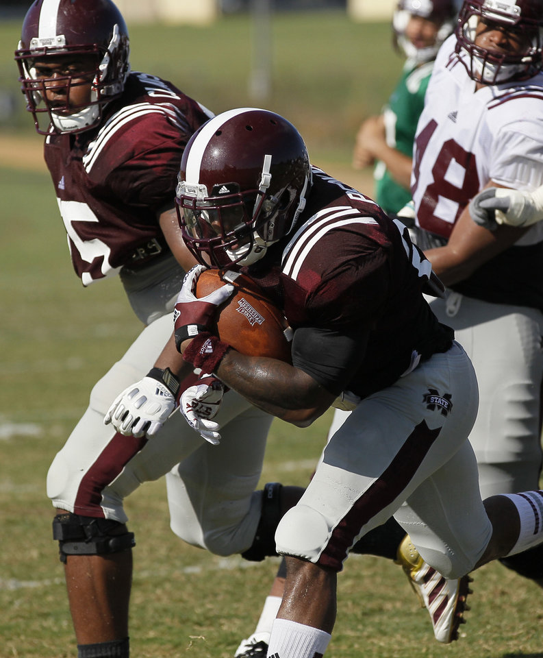 In this Aug. 10, 2013 photograph, Mississippi State football running back LaDarius Perkins, center, takes advantage of a leading block by offensive tackle Blaine Clausell, left, to run past a defender during practice in Starkville, Miss. Perkins says he's ready to cement his legacy as one of the school's best running backs in his final season. With another 1,000-yard performance, Perkins would become the school's third all-time leading rusher behind Anthony Dixon and Jerious Norwood. (AP Photo/Rogelio V. Solis)  ORG XMIT: JX201