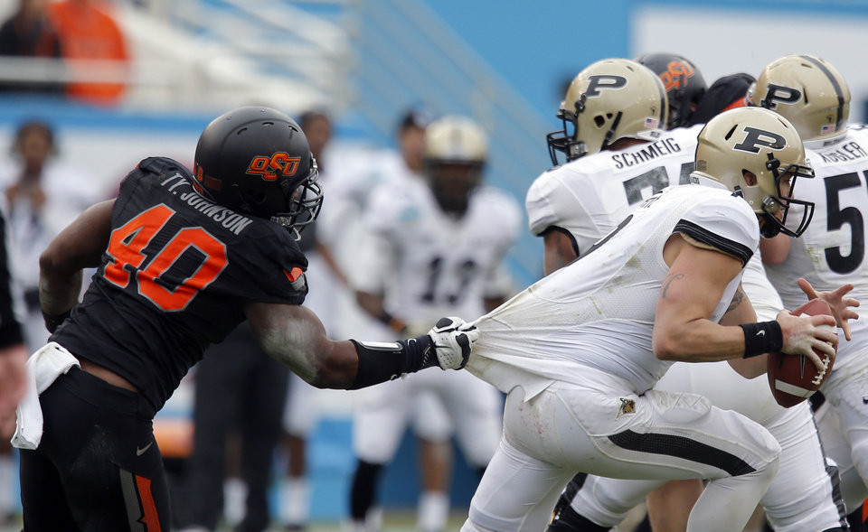 Photo - COLLEGE FOOTBALL / BOWL GAME: Oklahoma State's Tyler Johnson (40) pulls down Purdue's Robert Marve (9) during the Heart of Dallas Bowl football game between Oklahoma State University (OSU) and Purdue University at the Cotton Bowl in Dallas,  Tuesday,Jan. 1, 2013. Photo by Sarah Phipps, The Oklahoman