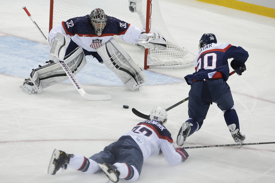 Photo - USA goaltender Jonathan Quick defends his goal against Slovakia forward Tomas Tatar as =22= slides across the ice during the 2014 Winter Olympics men's ice hockey game at Shayba Arena, Thursday, Feb. 13, 2014, in Sochi, Russia. (AP Photo/Matt Slocum)