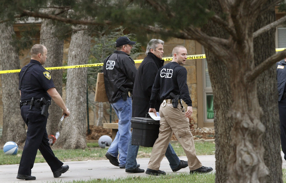 Pottawatomie County District Attorney Richard Smothermon, wearing overcoat, walks with a Shawnee police officer and crime scene investigators toward the front of a home where a dead woman was found inside. Shawnee police investigate the scene of a pre-dawn homicide in an upscale neighborhood in northeast Shawnee Thursday, March 21, 2013.  Police confirmed that Cathy Byus was killed in a domestic-related homicide inside her home at 27 Bella Vista Vista Lane.   Photo by Jim Beckel, The Oklahoman