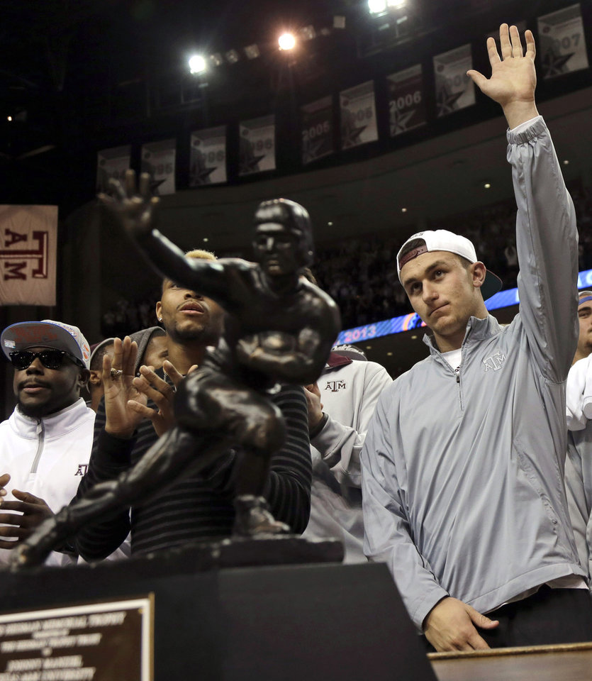 Texas A&M quarterback Johnny Manziel, right, waves to the crowd as he stands behind his Heisman Trophy as the team is acknowledged during halftime of Florida and Texas A&M NCAA college basketball game on Thursday, Jan. 17, 2013, in College Station, Texas. (AP Photo/David J. Phillip)