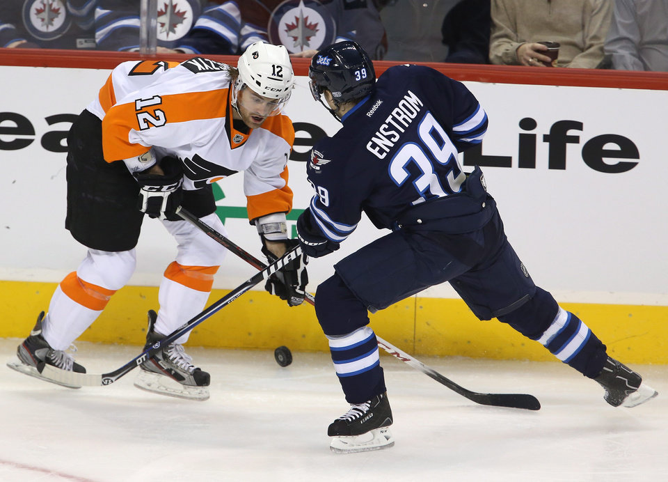 Photo - Philadelphia Flyers' Harry Zolnierczyk (12) and Winnipeg Jets' Tobias Enstrom (39) battle for control of the puck during the second period of an NHL hockey game in Winnipeg, Manitoba, Tuesday, Feb. 12, 2013. (AP Photo/The Canadian Press, Trevor Hagan)