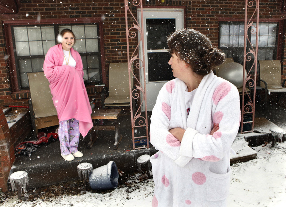 Photo - Cami Ericksen, 13, and her mother Tammy come out on their porch to watch firemen clear the street on Friday, Jan. 29, 2010, in Purcell, Okla. They have had no power or heat in their house since 2:00 pm. Thursday after a winter storm.  Photo by Steve Sisney, The Oklahoman