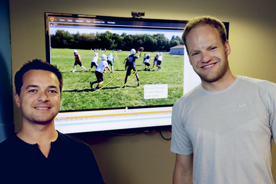 Photo - In this photo from Aug. 14, 2014, David Graff, CEO of Hudl, right, and John Wirtz, Chief Product Officer, pose for a photo in front of a screen showing their company's product, in Lincoln, Neb. Hudl is a software company that has developed a way to immediately get game film to coaches after games and break down and separate different plays by type. (AP Photo/Nati Harnik)