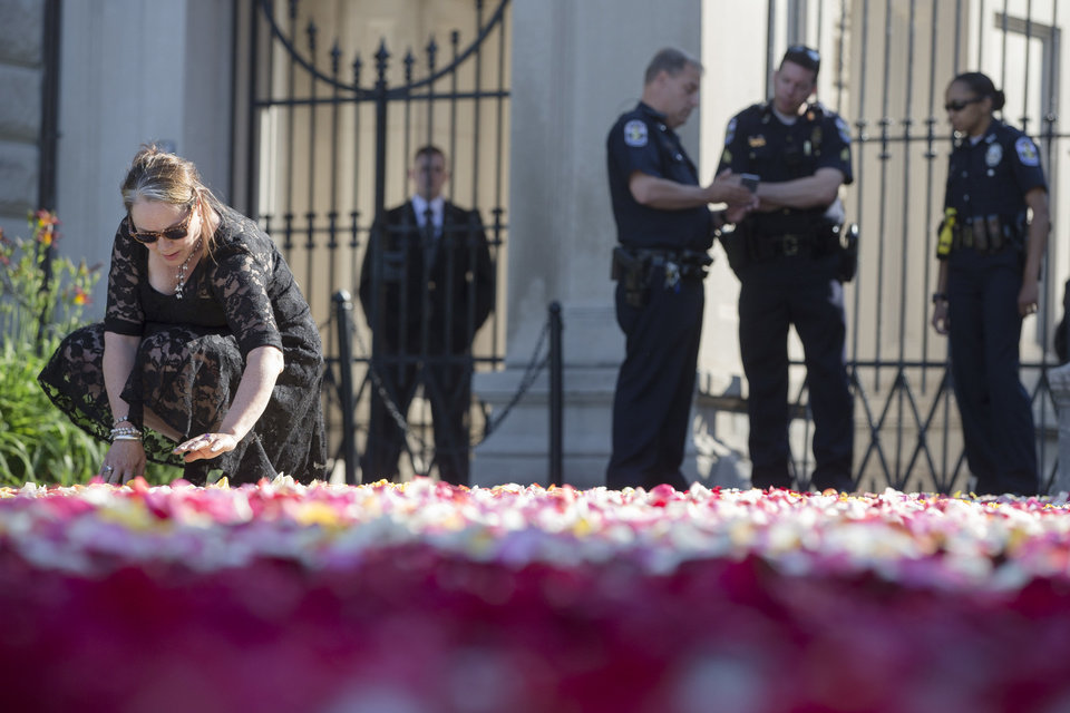 Photo - Maggie Cassaro, of Louisville, spreads roses along the entrance way to Cave Hill Cemetery as police stand guard before the arrival of Muhammad Ali's funeral procession, Friday, June 10, 2016, in Louisville, Ky.   Ali died last Friday at age 74 after a long battle with Parkinson's disease. (AP Photo/John Minchillo)