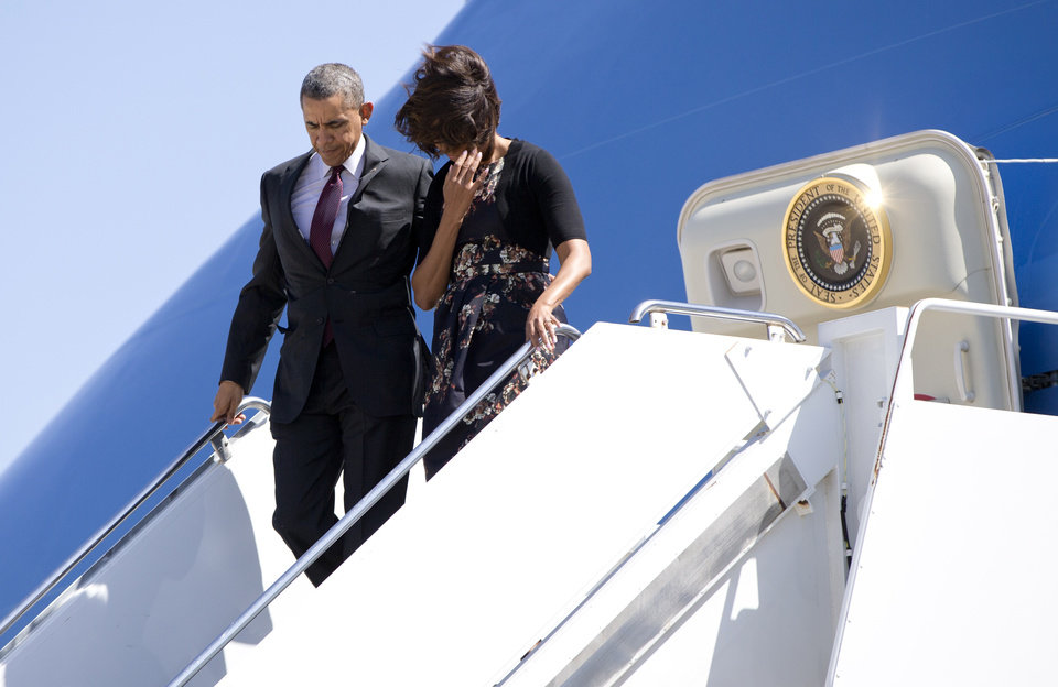 Photo - President Barack Obama and first lady Michelle Obama get off Air Force One upon their arrival at Robert Gray Army Air Field in Killeen, Texas, Wednesday, April 9, 2014, before traveling to Fort Hood for a memorial service for those killed there in a shooting last week. (AP Photo/Carolyn Kaster)