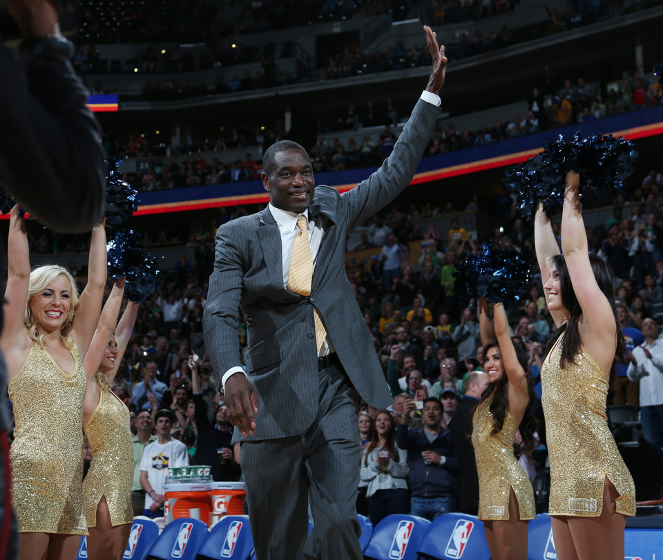 Photo - Former Denver Nuggets center Dikembe Mutombo waves to crowd as he is introduced during halftime ceremony to honor the players and coaches on the 1994 Denver team that upset top-seed Seattle SuperSonics in the opening round of the NBA Playoffs on Monday, March 17, 2014, in Denver.  The ceremony was staged during halftime of the Nuggets' 110-100 victory over the Los Angeles Clippers. (AP Photo/David Zalubowski)