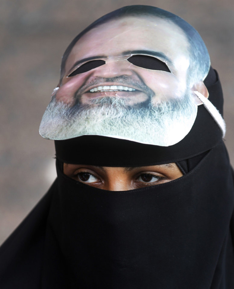 FILE - In this Wednesday, April 11, 2012 file photo, an Egyptian woman wears a mask of a potential candidate presidential candidate Hazem Abu Ismail as she attends a support rally outside a courtroom in Cairo, Egypt. Internal divisions are threatening to unravel Egypt�s second biggest political party, the political arm of the ultraconservative Salafis, the country�s most hardline Islamist movement. Now its leaders are split over whether Muslim clerics or more pragmatic politicians should be steering the movement. (AP Photo/Khalil Hamra, File)