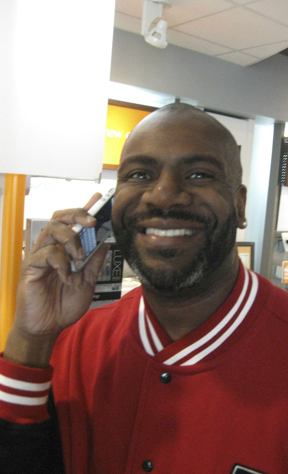 Photo - Charles Hopgood puts his new iPhone 5 to work moments after buying it at an AT&T store in northwest Oklahoma City. Hopgood upgraded from an iPhone 4.  DON MECOY - THE OKLAHOMAN