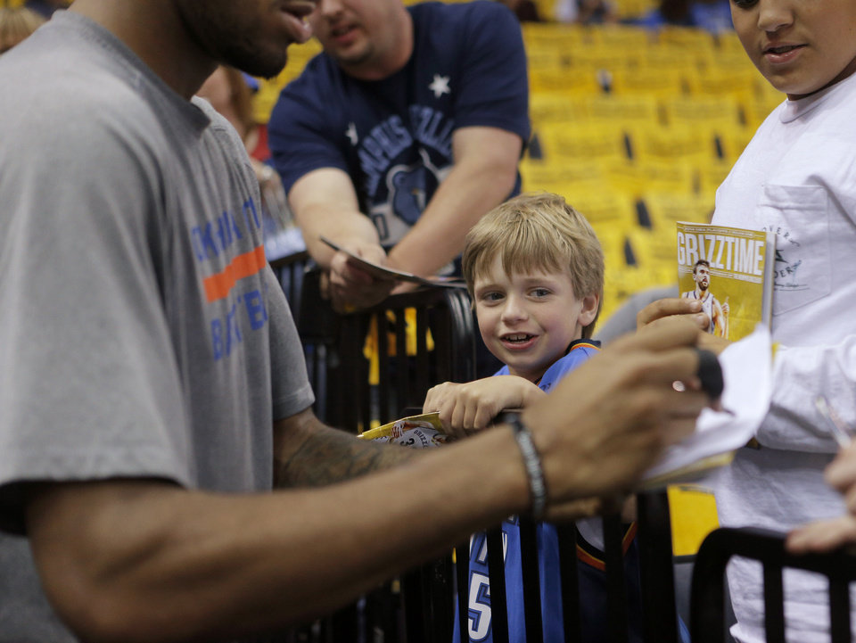 Photo - Tyler Stewart, 7, of Murfreesboro Tenn., smiles after Perry Jones of the Oklahoma City Thunder signed his shirt before Game 3 in the first round of the NBA playoffs between the Oklahoma City Thunder and the Memphis Grizzlies at FedExForum in Memphis, Tenn., Thursday, April 24, 2014. PHOTO BY BRYAN TERRY, The Oklahoman