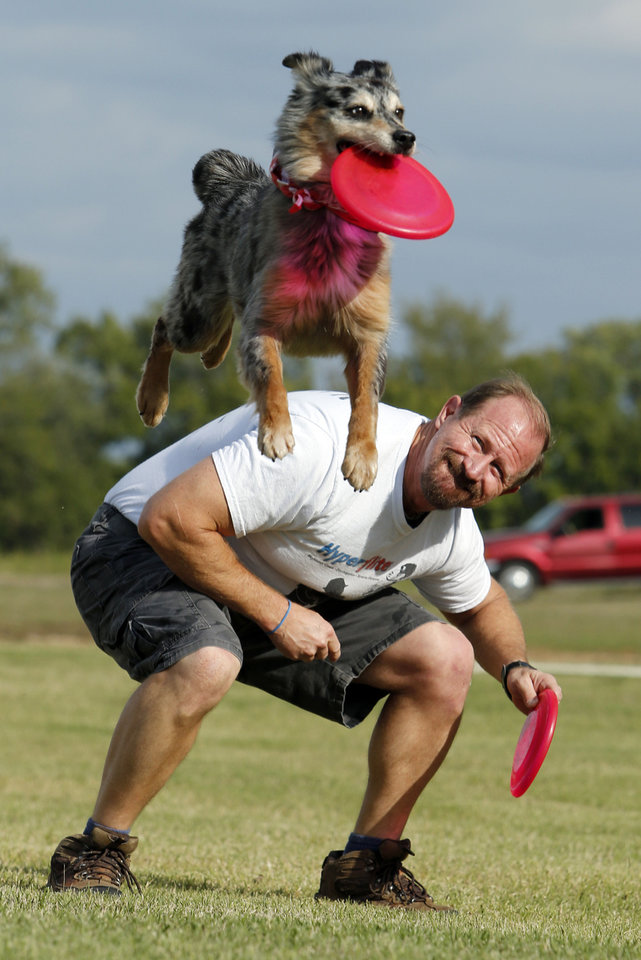 Photo - Lee Fairchild and his dog Gracie demonstrate their dog disc skills recently in Goldsby.  Photo by Steve Sisney, The Oklahoman  STEVE SISNEY