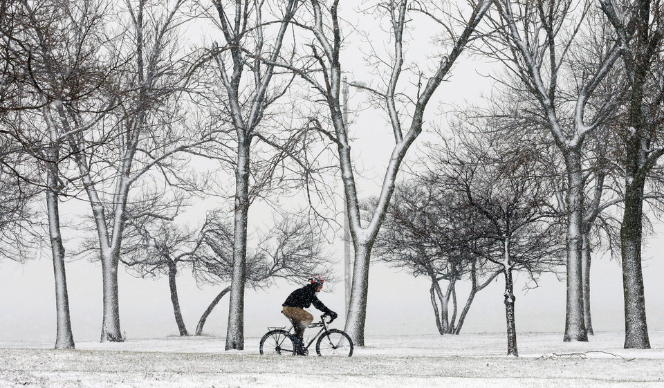 Photo - A lone cyclist navigates the bike path through a snow storm at Chicago's North Ave. beach Thursday, Dec. 27, 2012. A muted version of the deadly winter storm that has killed more than a dozen across the eastern half of the country reached the Northeast on Thursday, limiting most of its wrath to travel headaches as Christmas revelers tried to return home.  (AP Photo/Charles Rex Arbogast)