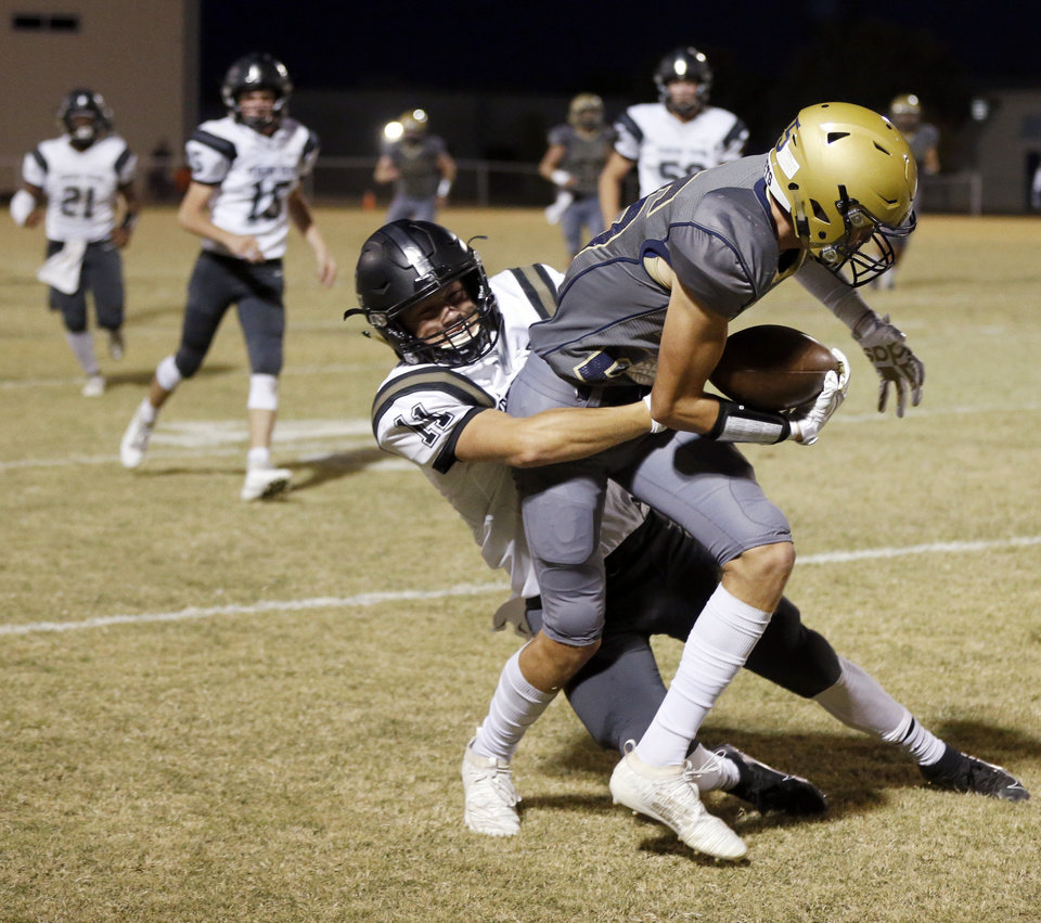 Photo - Kingfisher's Jarret Birdwell (25) is tackled by Perkins-Tryon's Cole Aldridge (11) after a catch during a high school football game between Perkins-Tryon and Kingfisher in Kingfisher, Okla., Thursday, Oct. 17, 2019. [Nate Billings/The Oklahoman]