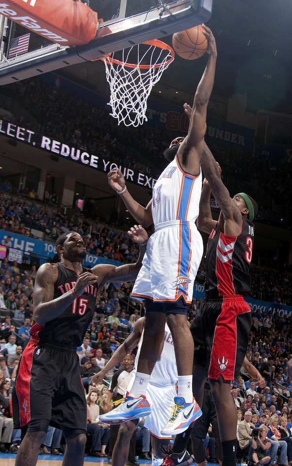 Photo - Oklahoma City's James Harden (13) shoots a lay up in front of Toronto's Amir Johnson (15) and Ed Davis (32) during the NBA basketball game between the Oklahoma City Thunder and the Toronto Raptors at Chesapeake Energy Arena in Oklahoma City, Sunday, April 8, 2012. Photo by Sarah Phipps, The Oklahoman.