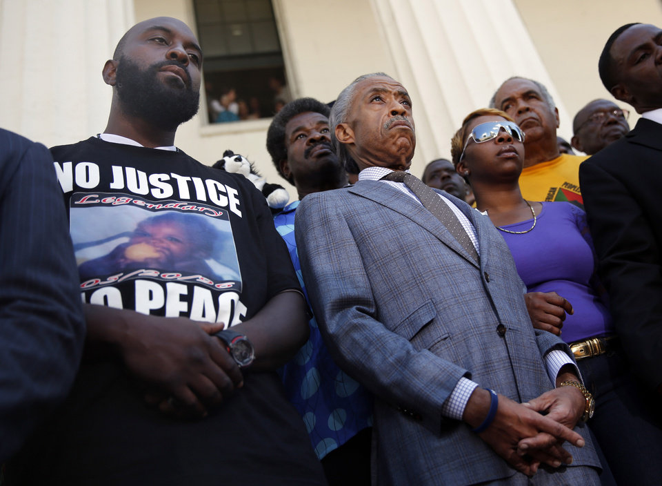 Photo - FILE - In this Aug. 12, 2014 file photo, civil rights leader Rev. Al Sharpton, center, stands with the parents of Michael Brown, Lesley McSpadden, right, and Michael Brown Sr., left, during a news conference outside the Old Courthouse in St. Louis. Lingering questions about Michael Brown could be answered Wednesday as two news organizations seek the release of any possible juvenile records for the unarmed 18-year-old who was shot by a police officer last month. (AP Photo/Jeff Roberson, File)
