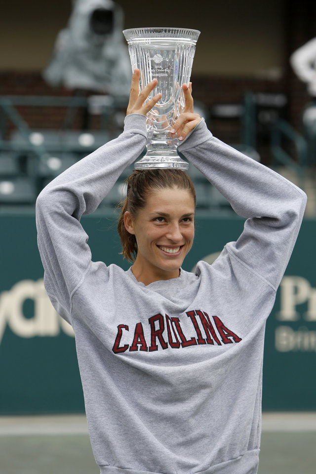 Photo - Andrea Petkovic, of Germany, holds the trophy while wearing a University of South Carolina sweatshirt after defeating Jana Cepelova, of Slovakia, in two sets during the Family Circle Cup tennis tournament final in Charleston, S.C., Sunday, April 6, 2014. Petkovic won 7-5, 6-2 to win the championship. Petkovic's father played tennis for South Carolina. (AP Photo/Mic Smith)