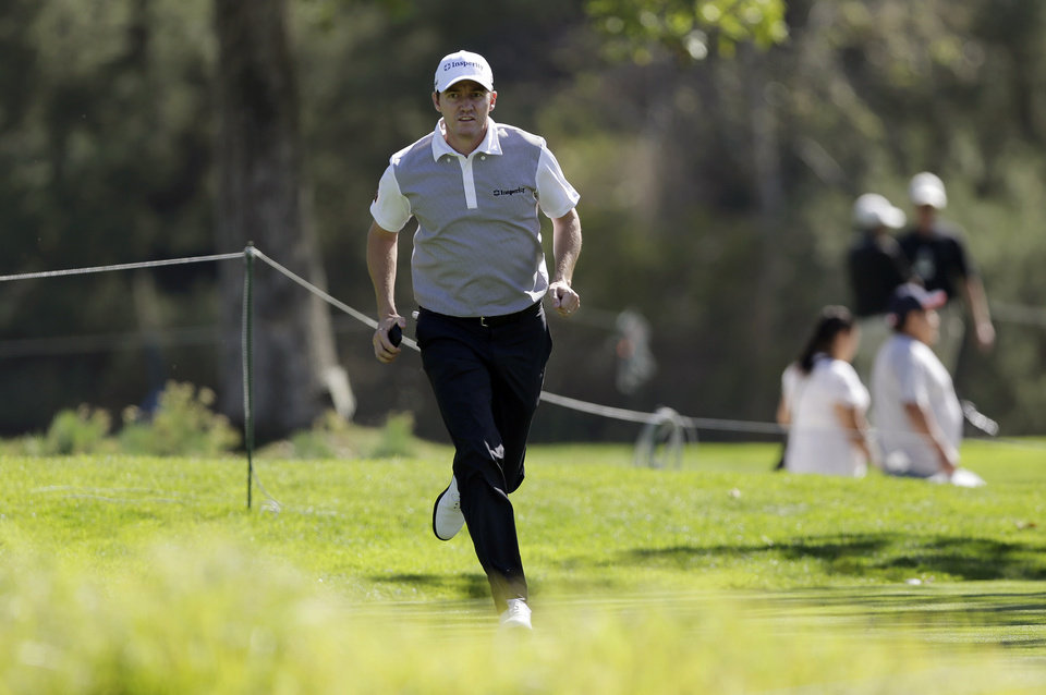 Photo - Jimmy Walker, winner of three tournaments so far this year, runs to the 14th tee in the pro-am of the Northern Trust Open golf tournament at Riviera Country Club in the Pacific Palisades area of Los Angeles on Wednesday, Feb. 12, 2014.  (AP Photo/Reed Saxon)