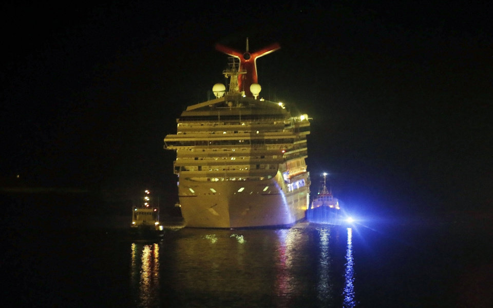 Photo - The cruise ship Carnival Triumph is towed up the Mobile River in Mobile, Ala., Thursday, Feb. 14, 2013. The ship with more than 4,200 passengers and crew members has been idled for nearly a week in the Gulf of Mexico following an engine room fire. (AP Photo/Dave Martin)
