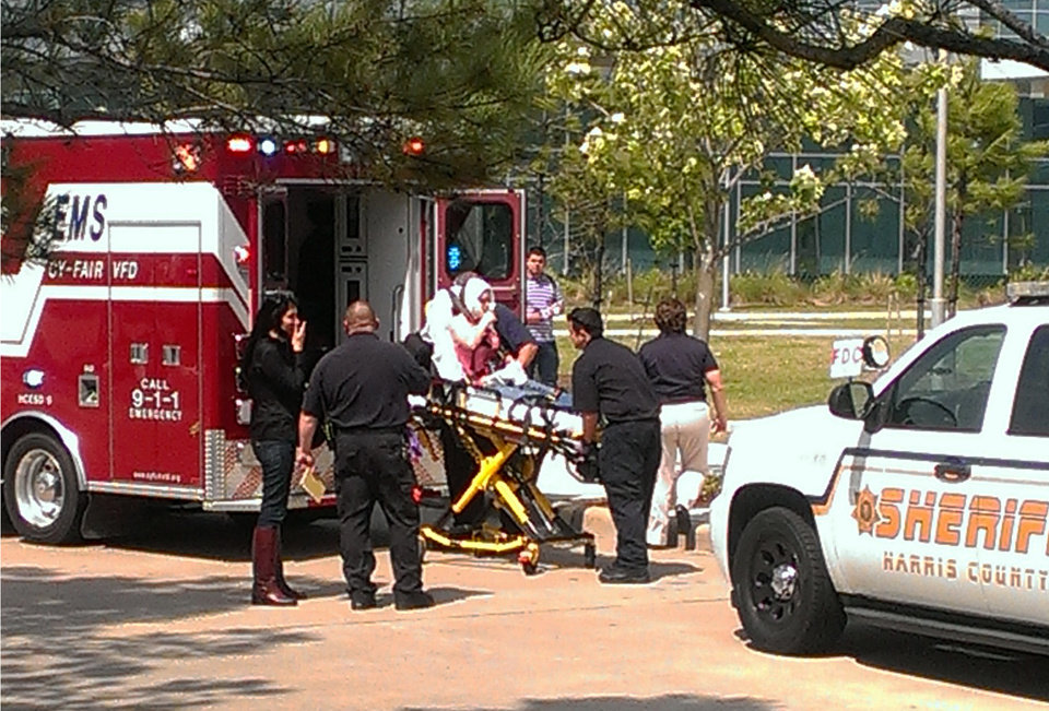 Photo - In this photo provided by Teaundrae Perryman, a victim is loaded into an ambulance after being wounded in a stabbing attack on the Lone Star community college system's Cypress, Texas campus Tuesday, April 9, 2013. At least 14 people were wounded when a suspect went building-to-building in an apparent stabbing attack at the college campus authorities said. (AP Photo/Teaundrae Perryman)