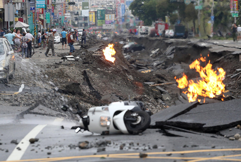 Photo - Vehicles are left lying on a destroyed street as part of the street is burning with flame following multiple explosions from an underground gas leak in Kaohsiung, Taiwan, early Friday, Aug. 1, 2014. Several underground gas explosions ripped through Taiwan's second-largest city overnight, hurling concrete through the air and blasting long trenches in the streets, authorities said Friday. (AP Photo) TAIWAN OUT