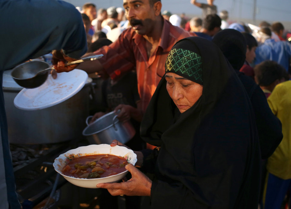Photo - In this Sunday, June 29, 2014 photo, a displaced Iraqi woman and others receive food from an Iraqi charity organization for a sunset meal when Muslims break their fast, on the first day of the Islamic holy month of Ramadan, at a camp for displaced Iraqis who fled from Mosul and other towns, in the Khazer area outside Irbil, northern Iraq. The grueling fast, in which observant Muslims abstain from water, food and cigarettes from sunrise to sunset, has been made even harsher for many living in dusty, hot tents. (AP Photo/Hussein Malla)
